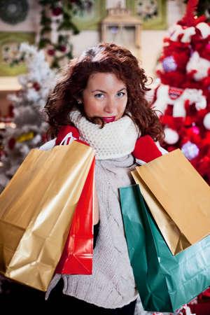 巻き毛の赤い髪とクリスマスのバッグを持つ女性