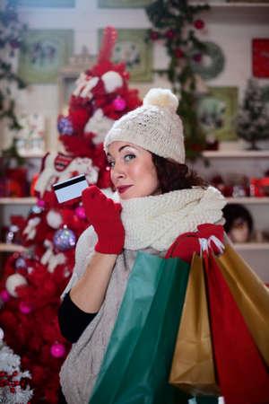 かわいい女の子があなたのクレジット カードを披露しながら変な顔を作る
