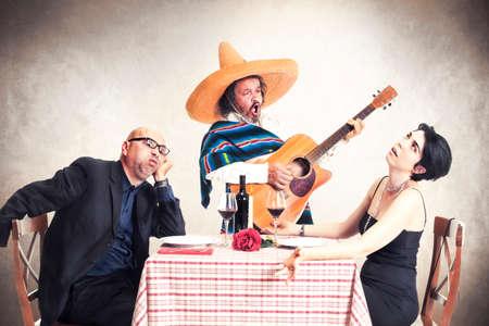 メキシコのミュージシャンに耳を傾けるディナー oblyed で退屈夫婦