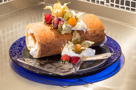 roll with whipped cream on blue plate Stock Photo