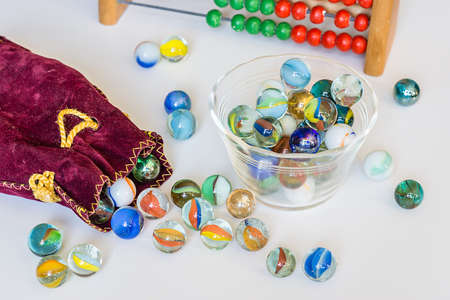 Open bag with glass balls on white table