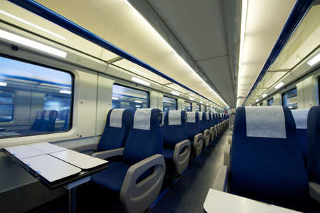 compartments: Empty interior of a passenger train car  aka coach or carriage   Rows of unoccupied seats and folding tables in economy or second class   Public transport  Editorial