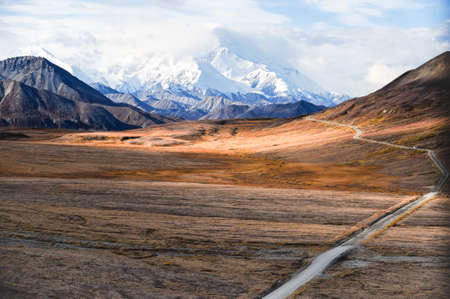 Mount McKinley s snowy peak with the park road and tundra in the foreground, Denali National Park, Alaska, US Stock Photo
