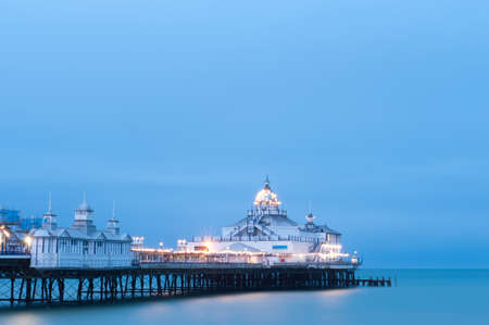 Eastbourne Pier illuminated at dusk, East Sussex, England, UK   Eastbourne is a well-known English seaside vacation destination or holiday resort Stock Photo