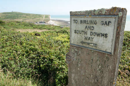 tout: Old sign to Birling Gap on the South Downs Way, with Belle Tout lighthouse and Birling Gap  Stock Photo