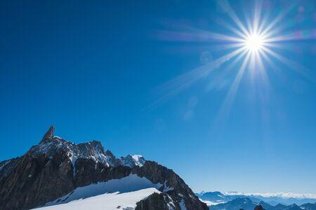 Dente Del Gigante in the blue sky with Sun