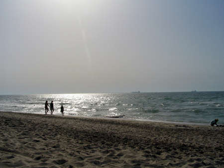A beach view in Dubai, afternoon with silouettes of people walking on the sand relaxed Stock Photo