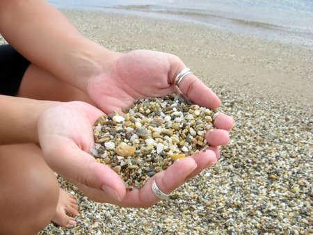 Female hands full of pebbles in the beach Stock Photo