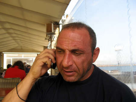 unshaved: Middleaged man, unshaved talking to the mobile phone