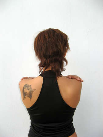 Young womans back with brown short hair and arms on her shoulders