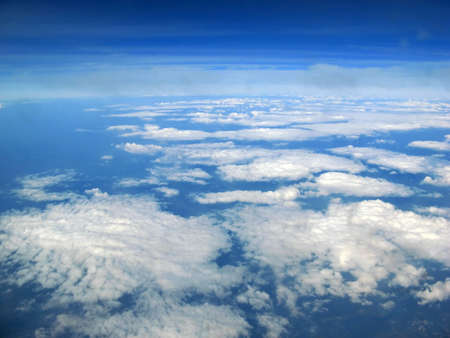Blue sky above the clouds while flying under the sun Stock Photo