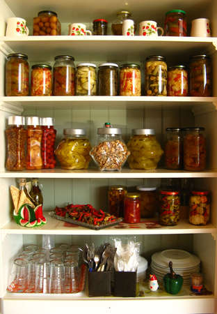 A white kitchen cabinet full of jars, sauces and bottles