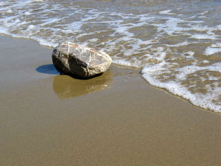 A bib stone on the sand getting wet from the sea