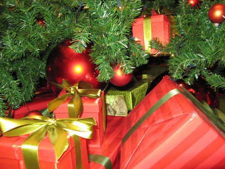Part of a Christmas tree full of presents and red shiny balls Stock Photo