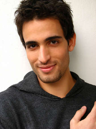 A young man is looking at the camera isolated on a white background