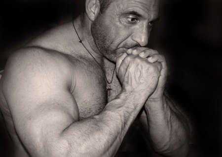 mascular: A body builder sitting side at the camera with his hands on his face in black and white