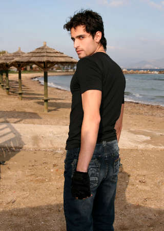 mascular: A handsome man at the beach looking back