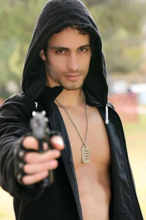 An attractive young man holding a gun