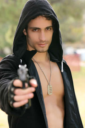 An attractive young man holding a gun