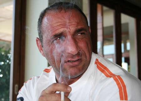 A man around 40 smoking a cigarette photo