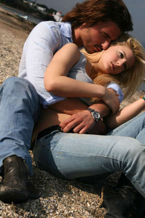 A young couple in love hugging on the beach Stock Photo