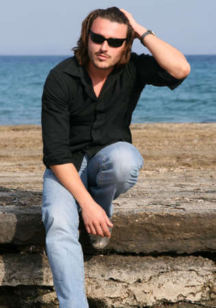 beach hunk: Blonde young man with sunglasses sitting on a rock