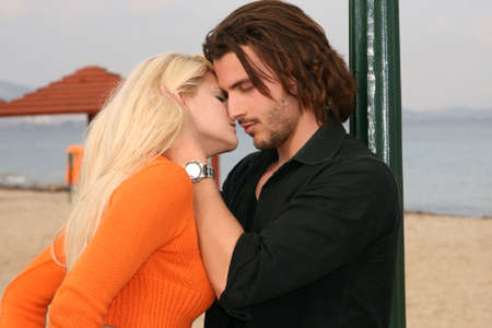 man woman kissing: Young blonde couple kissing at the beach Stock Photo
