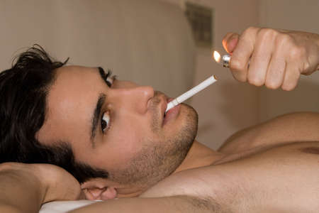 Man lying on the bed lighting a cigarette Stock Photo