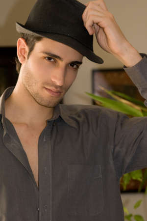 Young handsome man wearing a black hat