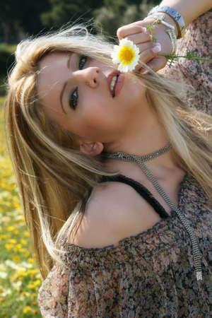 Beautiful blonde woman holding a daisy Stock Photo