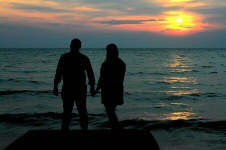 silhoutte: the silhoutte of couple at jetty during sunset