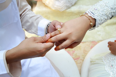 marriages: malay wedding groom bolstering gold ring on brides finger Stock Photo