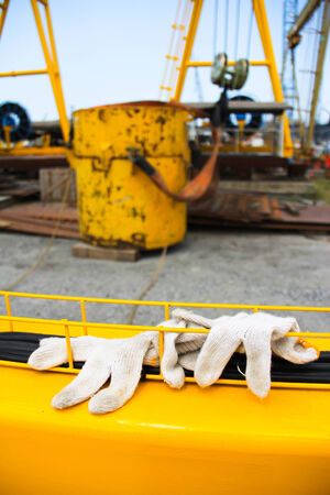 forground: This is experimental lifting hook on background and gloves on forground Stock Photo