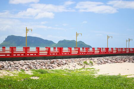 extends: The bridge extends to the sea with blue sky. Stock Photo