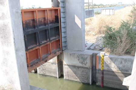 floodgates: Floodgates a concrete building in the countryside, water level. Stock Photo
