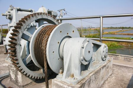 Machine is rusty cogs of the floodgates in rural areas, with asphalt roads Stock Photo
