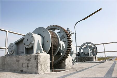 rural areas: Machine is rusty cogs of the floodgates in rural areas, with asphalt roads Stock Photo