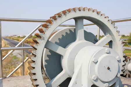 floodgates: Machine is rusty cogs of the floodgates in rural areas, with asphalt roads Stock Photo