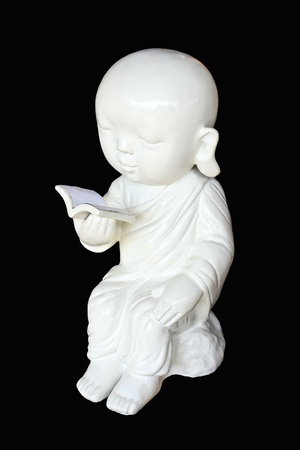 Sculpture of white neophyte in a sitting and reading posture on black background photo