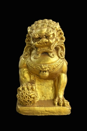 Sculpture of golden male lion holds the ball on a black ground, symbol of guardian and protection.  photo