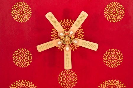 Ceiling fan with five lights on a red ceiling with Thai painted. photo