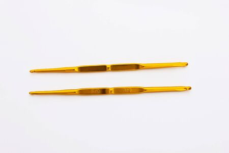 Number 5 and 7 of golden crochet hooks on a white background for knit dolls, bags, etc. photo