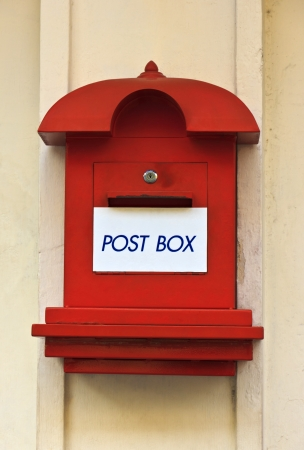 Red post box on cement wall  photo