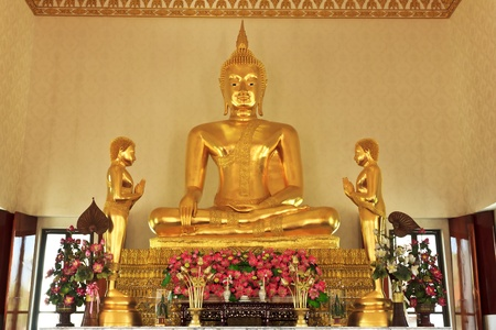 gautama: The sculpture of golden principal buddha with two disciples of Gautama Buddha stands on the left and right