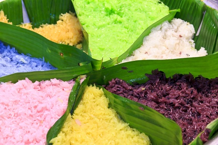 Sweet herb sticky rice in 7 colors on banana leaf, commonly with ripe mango, shred coconut, dried fish or shrimp, and Thai custard etc  photo