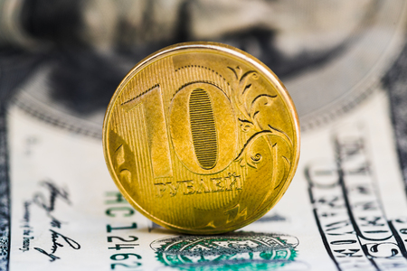 Russian coin in denominations of 10 rubles on the background of the 100 dollar bill