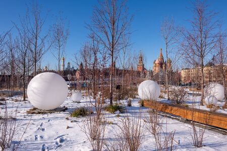 Moscow, Russia - February 8, 2020: View of the Moscow Kremlin, Ivan the Great Bell-Tower, Spasskaya tower and St. Basil's Cathedral from Zaryadye Park on sunny winter day. In the foreground Large ball-shaped lanterns.