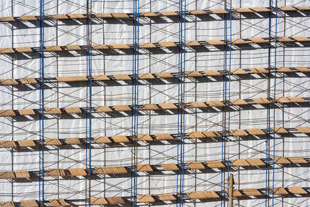 Scaffolding background on a construction site. Spring sunny day