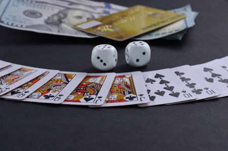 Playing cards, dices and money on a black background.