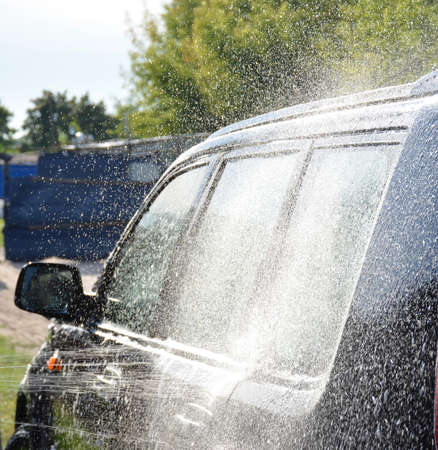 Black car washed with shampoo. Dirt water by car.